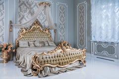 Κρεβατοκάμαρα πολυτέλειας στα ελαφριά χρώματα με τις χρυσές λεπτομέρειες επίπλων Μεγάλο άνετο διπλό βασιλικό κρεβάτι στον κομψό κ Στοκ φωτογραφία με δικαίωμα ελεύθερης χρήσης