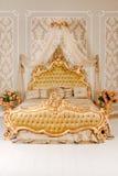 Κρεβατοκάμαρα πολυτέλειας στα ελαφριά χρώματα με τις χρυσές λεπτομέρειες επίπλων Μεγάλο άνετο διπλό βασιλικό κρεβάτι στον κομψό κ Στοκ Εικόνα