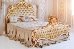 Κρεβατοκάμαρα πολυτέλειας στα ελαφριά χρώματα με τις χρυσές λεπτομέρειες επίπλων Μεγάλο άνετο διπλό βασιλικό κρεβάτι στον κομψό κ Στοκ Εικόνες