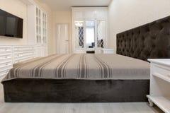 Κρεβατοκάμαρα στα ελαφριά χρώματα με τα ξύλινα άσπρα έπιπλα στοκ εικόνες