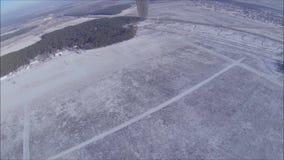 Κρεμάστε το ανεμοπλάνο απογειώνεται πέρα από ένα χιονώδη χειμερινά λιβάδι και ένα δάσος απόθεμα βίντεο
