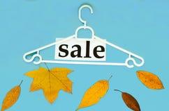 Κρεμάστρα, ξηρά, φύλλα και πώληση ` φθινοπώρου λέξης ` στο μπλε υπόβαθρο Στοκ εικόνα με δικαίωμα ελεύθερης χρήσης