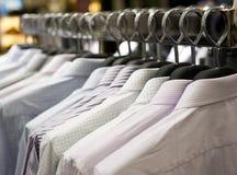Κρεμάστρες υφασμάτων με τα πουκάμισα Στοκ φωτογραφία με δικαίωμα ελεύθερης χρήσης