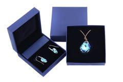 Κρεμαστό κόσμημα και σκουλαρίκι μπλε πετρών στο μπλε παρόν κιβώτιο Στοκ Εικόνα