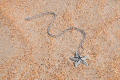 Κρεμαστό κόσμημα στην άμμο θάλασσας στοκ εικόνες