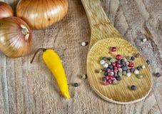 Κρεμμύδια και πιπέρι καρυκευμάτων στον ξύλινο πίνακα Στοκ Φωτογραφία