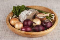 Κρεμμύδια, καφετής ξύλινος δίσκος ψωμιού με το μαϊντανό και άλας και σέλινο Στοκ φωτογραφία με δικαίωμα ελεύθερης χρήσης