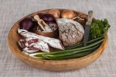 Κρεμμύδια, καφετής ξύλινος δίσκος ψωμιού με το μαϊντανό και άλας, σέλινο σαλαμιού, μαχαίρι Στοκ Φωτογραφία