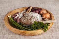 Κρεμμύδια, καφετής ξύλινος δίσκος ψωμιού με το μαϊντανό και άλας, σέλινο σαλαμιού, μαχαίρι Στοκ φωτογραφία με δικαίωμα ελεύθερης χρήσης