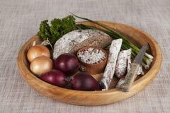 Κρεμμύδια, καφετής ξύλινος δίσκος ψωμιού με το μαϊντανό και άλας, σέλινο σαλαμιού, μαχαίρι Στοκ εικόνα με δικαίωμα ελεύθερης χρήσης