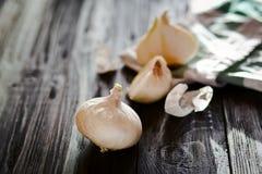 Κρεμμύδια σε έναν σκοτεινό ξύλινο πίνακα Στοκ Φωτογραφίες