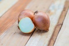 Κρεμμύδια στον ξύλινο πίνακα Στοκ Εικόνα