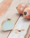 Κρεμμύδια στον ξύλινο πίνακα Στοκ Εικόνες