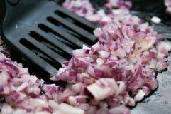 Κρεμμύδι ανακατώνω-που τηγανίζεται σε ένα τηγάνι Στοκ Εικόνες