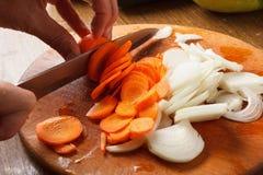 Κρεμμύδι και καρότο περικοπών στον τεμαχίζοντας πίνακα Στοκ Φωτογραφία