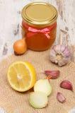 Κρεμμύδι, σκόρδο, λεμόνι και μέλι στο βάζο γυαλιού, υγιής διατροφή και ενίσχυση της ασυλίας στοκ φωτογραφία