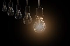 Κρεμώντας λάμπες φωτός με καμμένος μια στο σκοτεινό υπόβαθρο στοκ φωτογραφία με δικαίωμα ελεύθερης χρήσης