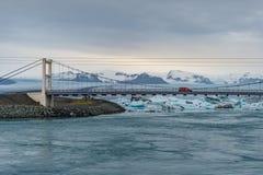 Κρεμώντας γέφυρα πέρα από τη στενή θάλασσα με τη λιμνοθάλασσα παγετώνων Jokulsarlon και το βουνό χιονιού Στοκ Εικόνα