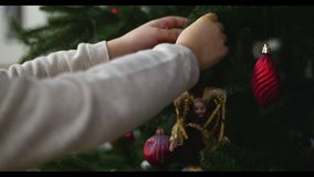 Κρεμώντας διακοσμήσεις Χριστουγέννων σε ένα δέντρο με τα φω'τα Χριστουγέννων Τα χέρια ενός μικρού κοριτσιού διακοσμούν ένα χριστο απόθεμα βίντεο
