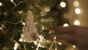 Κρεμώντας διακόσμηση Χριστουγέννων στο δέντρο με τα φω'τα Χριστουγέννων απόθεμα βίντεο