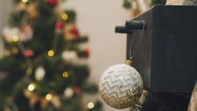 Κρεμώντας διακόσμηση Χριστουγέννων στο δέντρο με τα φω'τα Χριστουγέννων Διακόσμηση στο χριστουγεννιάτικο δέντρο με τη σφαίρα φιλμ μικρού μήκους