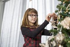 Κρεμώντας διακόσμηση έφηβη στο χριστουγεννιάτικο δέντρο στο σπίτι Στοκ εικόνες με δικαίωμα ελεύθερης χρήσης