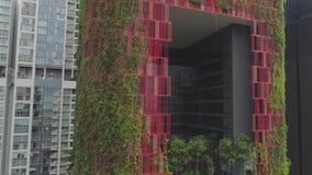 Κρεμώντας κήποι στο κόκκινο όμορφο ξενοδοχείο στη Σιγκαπούρη πλάνο Τοπ άποψη του κόκκινου κτηρίου με την πρασινάδα στη Σιγκαπούρη απόθεμα βίντεο