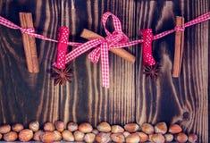 Κρεμώντας κανέλα και anises σε ένα σχοινί και τα φουντούκια σε ένα ξύλινο υπόβαθρο Στοκ εικόνα με δικαίωμα ελεύθερης χρήσης