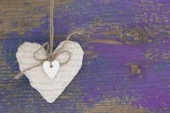 Κρεμώντας καρδιά και πορφυρό ξύλινο υπόβαθρο στο ύφος χωρών. Στοκ εικόνα με δικαίωμα ελεύθερης χρήσης
