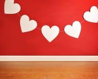 Κρεμώντας καρδιές ημέρας βαλεντίνου στο κόκκινο υπόβαθρο στοκ εικόνες