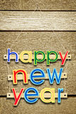 Κρεμώντας κείμενο καλή χρονιά χαιρετισμού στα ξύλα Στοκ Εικόνες