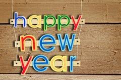 Κρεμώντας κείμενο καλή χρονιά χαιρετισμού στο ξύλινο υπόβαθρο Στοκ Φωτογραφίες