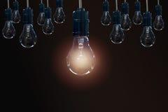 Κρεμώντας λάμπες φωτός με καμμένος μια στο σκοτεινό υπόβαθρο Ιδέα στοκ φωτογραφίες