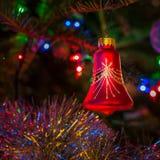 Κρεμώντας μπιχλιμπίδι χριστουγεννιάτικων δέντρων μεταξύ των λαμπρών φω'των υποβάθρου στοκ φωτογραφία