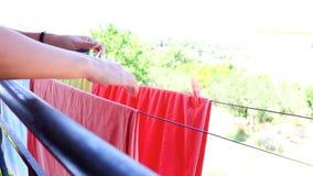 Κρεμώντας πετσέτες γυναικών και σεντόνια που ξεραίνουν στο μπαλκόνι Τα θηλυκά χέρια στερεώνουν την πλύση στη γραμμή Πλυντήριο σε  απόθεμα βίντεο