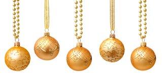 Κρεμώντας τις χρυσές σφαίρες Χριστουγέννων με την κορδέλλα που απομονώνεται Στοκ Εικόνες