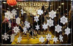 Κρεμώντας snowflakes Χριστουγέννων τσιγγελακιών στην έκθεση Στοκ Εικόνες