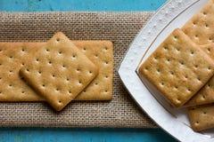 Κροτίδες μπισκότων σε ένα άσπρα πιατάκι και matting Στοκ Φωτογραφία
