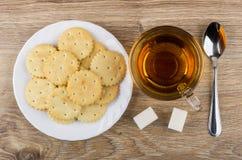 Κροτίδες στο πιάτο, το φλυτζάνι του τσαγιού, τη ζάχαρη και το κουταλάκι του γλυκού Στοκ φωτογραφία με δικαίωμα ελεύθερης χρήσης