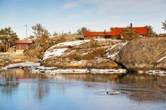 Κρυμμένος στους βράχους κόκκινο θερινό εξοχικό σπίτι, φιορδ το χειμώνα Στοκ Εικόνες