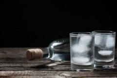 Κρύα βότκα στα πυροβοληθε'ντα γυαλιά σε ένα μαύρο υπόβαθρο Στοκ Φωτογραφίες