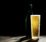 Κρύα μπύρα στο γυαλί και μπουκάλι πράσινο σε ένα ξύλινο υπόβαθρο Στοκ φωτογραφίες με δικαίωμα ελεύθερης χρήσης