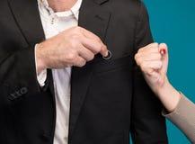 Κρύβοντας γαμήλιο δαχτυλίδι ανδρών, γυναίκα που παρουσιάζει του μια πυγμή στοκ εικόνα