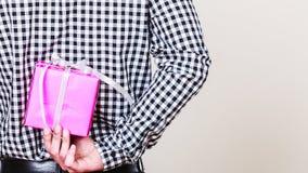 Κρύβοντας κιβώτιο δώρων ατόμων πίσω από την πλάτη Έκπληξη διακοπών Στοκ Εικόνες