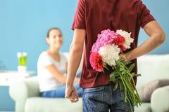 Κρύβοντας λουλούδια νεαρών άνδρων για τη φίλη πίσω από την πλάτη του στο εσωτερικό στοκ εικόνες με δικαίωμα ελεύθερης χρήσης