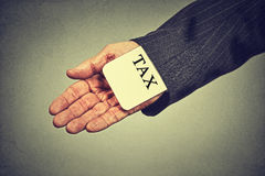 Κρύβοντας φορολογική κάρτα χεριών ατόμων σε ένα μανίκι ενός κοστουμιού έννοια οικονομίας φοροδιαφυγής Στοκ Εικόνες
