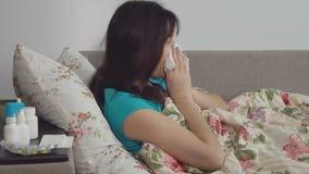 κρύες νεολαίες γυναικώ&n Κάθεται σε ένα κρεβάτι σε ένα κάλυμμα απόθεμα βίντεο