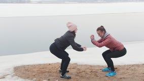 Κρύος καιρός Δύο λεπτές γυναίκες στα σακάκια που κάνουν τις στάσεις οκλαδόν στη χιονώδη παραλία απόθεμα βίντεο