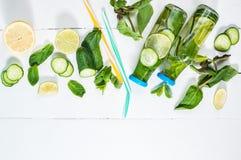 Κρύος και αναζωογόνηση που εμποτίζεται detox ποτίστε με τον ασβέστη, τη μέντα και το αγγούρι σε ένα μπουκάλι στο άσπρο ξύλινο υπό Στοκ φωτογραφία με δικαίωμα ελεύθερης χρήσης