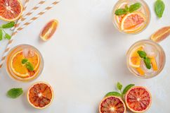 Κρύο αναζωογονώντας ποτό με τις φέτες πορτοκαλιών αίματος σε ένα γυαλί σε ένα άσπρο συγκεκριμένο υπόβαθρο Στοκ φωτογραφία με δικαίωμα ελεύθερης χρήσης